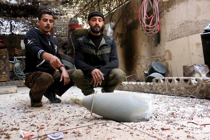 Syrian men sit next to an unexploded missile afteran Assad regime air attack on the opposition in the besieged town of