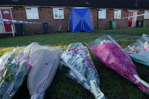 A police tent and floral tributes outside the home where Mylee was