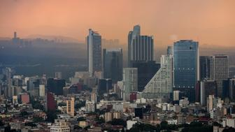 Smog hangs at dusk over downtown Mexico City, Mexico, on Thursday, Aug. 11, 2016. Mexico's push to reduce air pollution may set the stage for a surge in clean energy-related bond sales. For the first time, the government will auction $8 billion worth of clean energy projects this year, according to Pricewaterhouse Cooper. Photographer: Brett Gundlock/Bloomberg via Getty Images