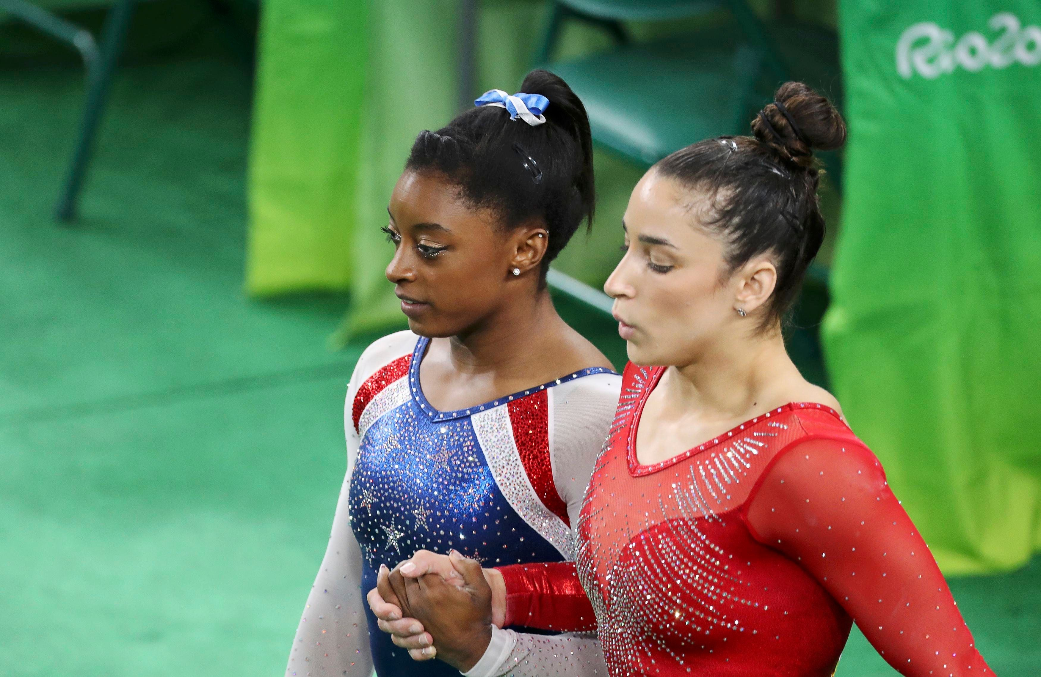 2016 Rio Olympics - Artistic Gymnastics - Final - Women's Individual All-Around Final - Rio Olympic Arena - Rio de Janeiro, Brazil - 11/08/2016. Simone Biles (USA) of USA (L) and Alexandra Raisman (USA) of USA (Aly Raisman) hold hands during the women's individual all-around final. REUTERS/Damir Sagolj FOR EDITORIAL USE ONLY. NOT FOR SALE FOR MARKETING OR ADVERTISING CAMPAIGNS