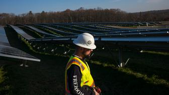 GRAFTON, MASSACHUSETTS - DECEMBER 4: Employees from a Radian Generation's operations and maintenance team change out a faulty solar inverter along a row of solar panels December 4, 2017 at the family-owned Knowlton Farm in Grafton, Massachusetts. The 3.7 megawatt solar array is owned and operated by BlueWave Solar which feeds the generated electricity to homes and small businesses in nearby municipalities. (Photo by Robert Nickelsberg/Getty Images)
