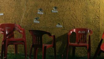 The chairs of a food stall stand next to a bullet-riddled wall with impact markers on it at a crime scene in Zapopan September 12, 2012. A man and a woman were shot dead by hitmen while they were eating, while a worker and another client of the food stall were injured, according to local media.  REUTERS/Alejandro Acosta (MEXICO  - Tags: CRIME LAW CIVIL UNREST)
