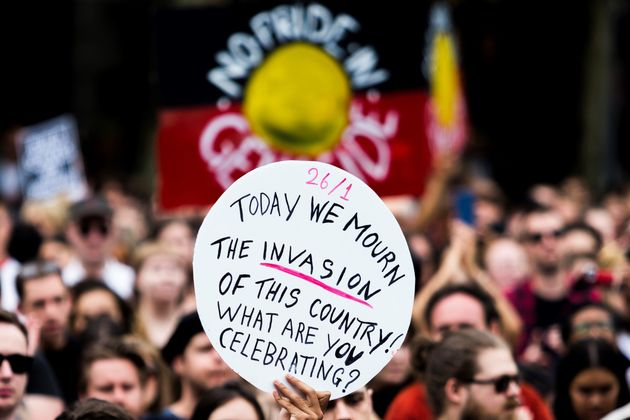 A protester holds a banner during a demonstration on Australia Day