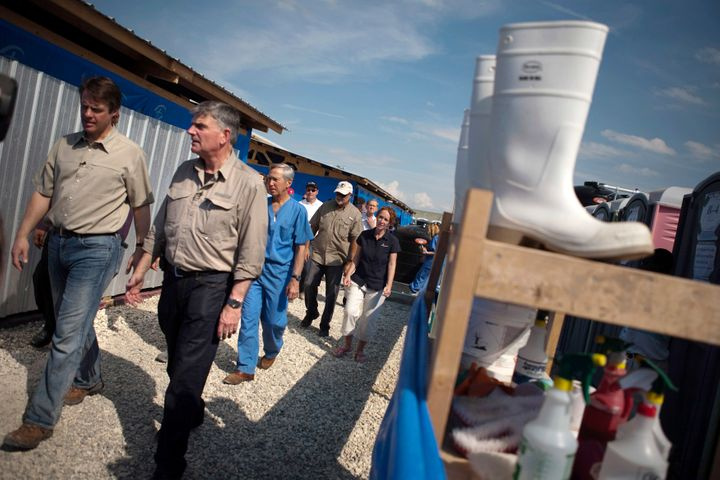 Graham (second from left) is the head of the international relief organization Samaritan's Purse. Here, he visits one of the organization's cholera treatment centers in Port-au-Prince, Haiti, in 2011.