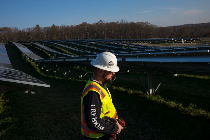 Employees from a Radian Generation's operations and maintenance team change out a faulty solar inverter along a row of solar