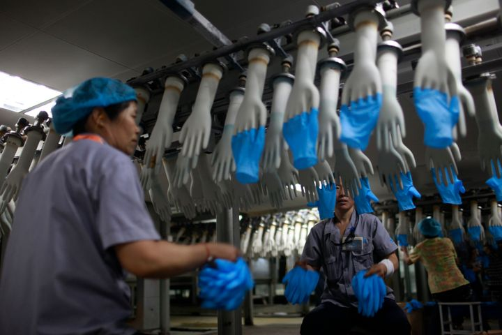 Workers on a rubber glove assembly line at a factory in Shandong Province, China.