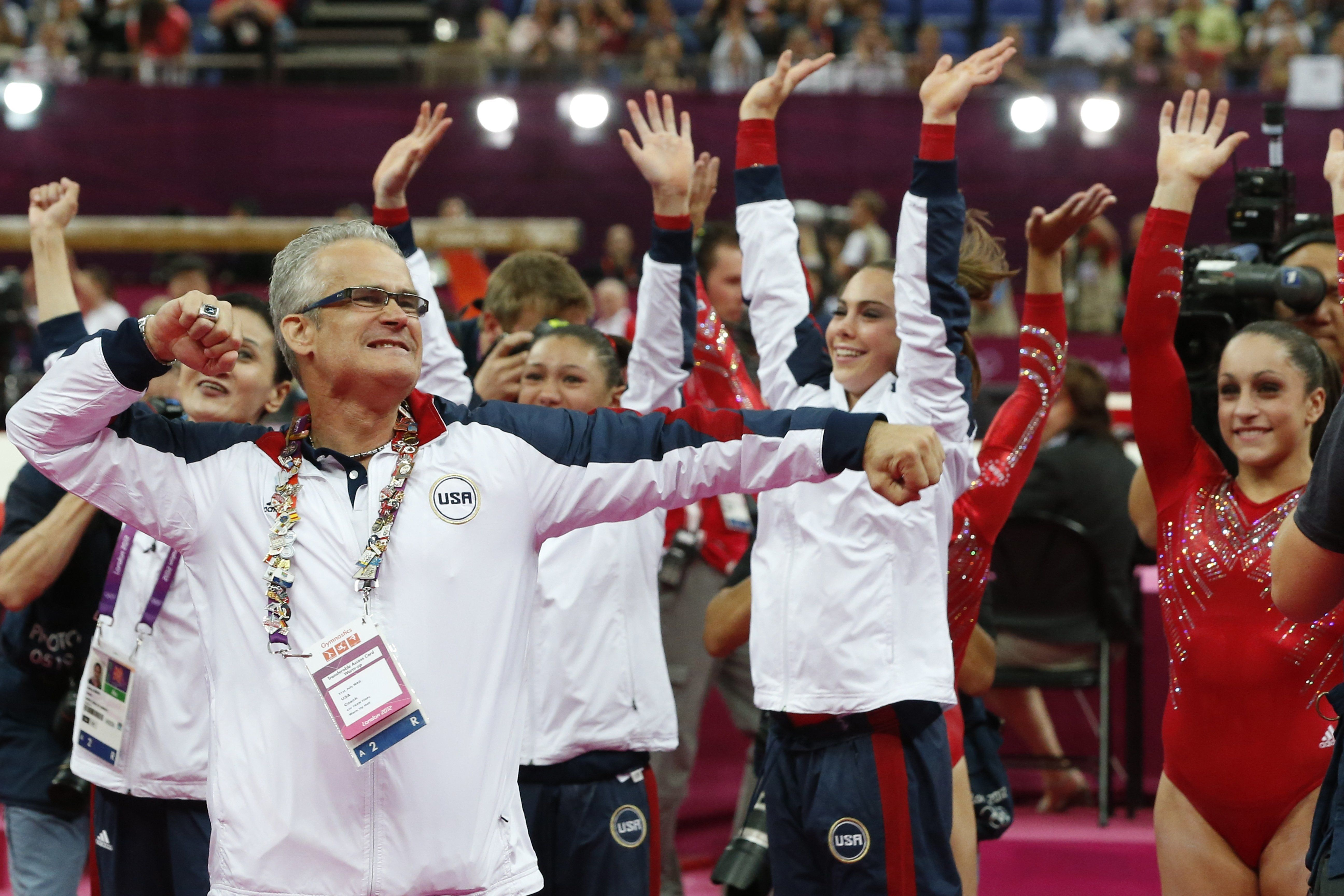 US women gymnastics team John Geddert celebrates with the team after the US  won gold in the women's team of the artistic gymnastics event of the London Olympic Games on July 31, 2012 at the 02 North Greenwich Arena in London. Team US won gold, Team Russia took silver and Team Romania got bronze.  AFP PHOTO / THOMAS COEX        (Photo credit should read THOMAS COEX/AFP/GettyImages)