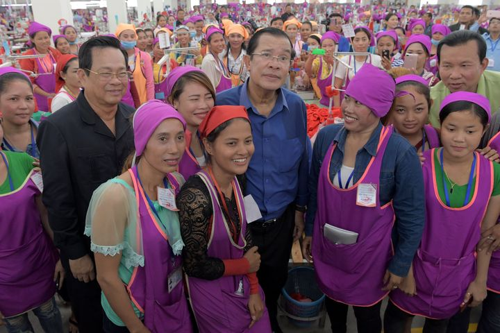 Cambodian Prime Minister Hun Sen, center, poses with garment workers at a factory on the outskirts of Phnom Penh.