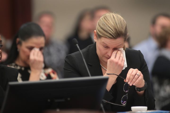 Gina Nichols, mother of victim Maggie Nichols, and Assistant Attorney General Angela Povilaitis wipe tears from their eyes as