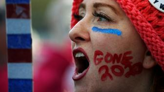 """Kelly Duncan chants with """"Gone 2020"""" slogan painted on her cheek as she participates in the Second Annual Women's March in Washington, U.S., January 20, 2018. REUTERS/Leah Millis"""