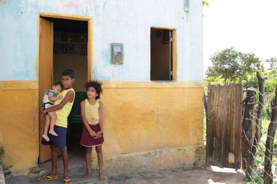 Three of Silva's children — Gabriel, 2;Paulo, 11; Paulina, 9 — stand outside the family's home.