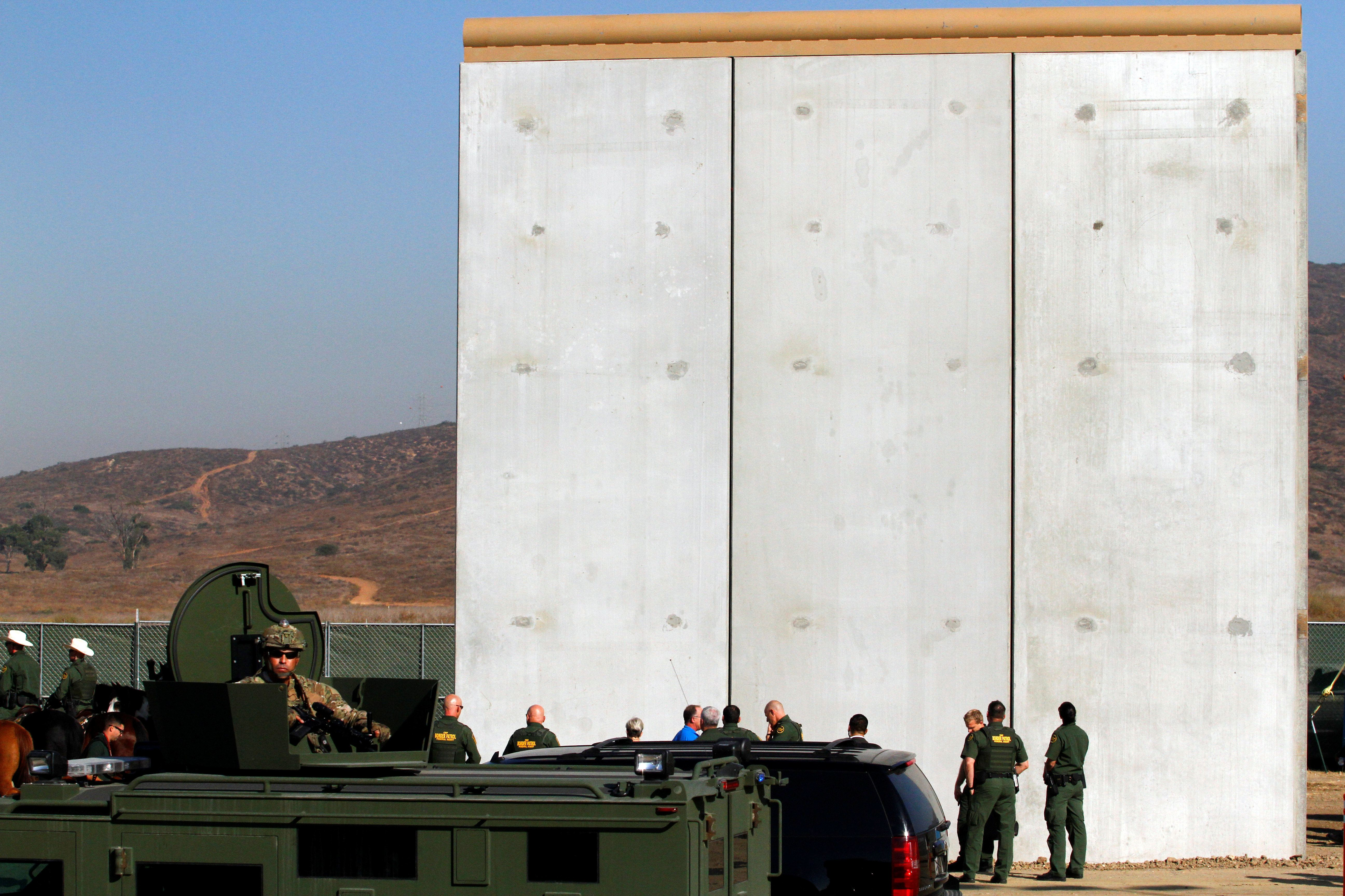 Border patrol authorities visit the site where several prototypes for U.S. President Donald Trump's border wall with Mexico have been built, in this picture taken from the Mexican side of the border, in Tijuana, Mexico, October 26, 2017. REUTERS/Jorge Duenes