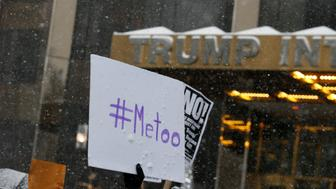 Protest signs are raised at #MeToo demonstration outside Trump International hotel in New York City, NY, U.S., December 9, 2017. REUTERS/Brendan McDermid