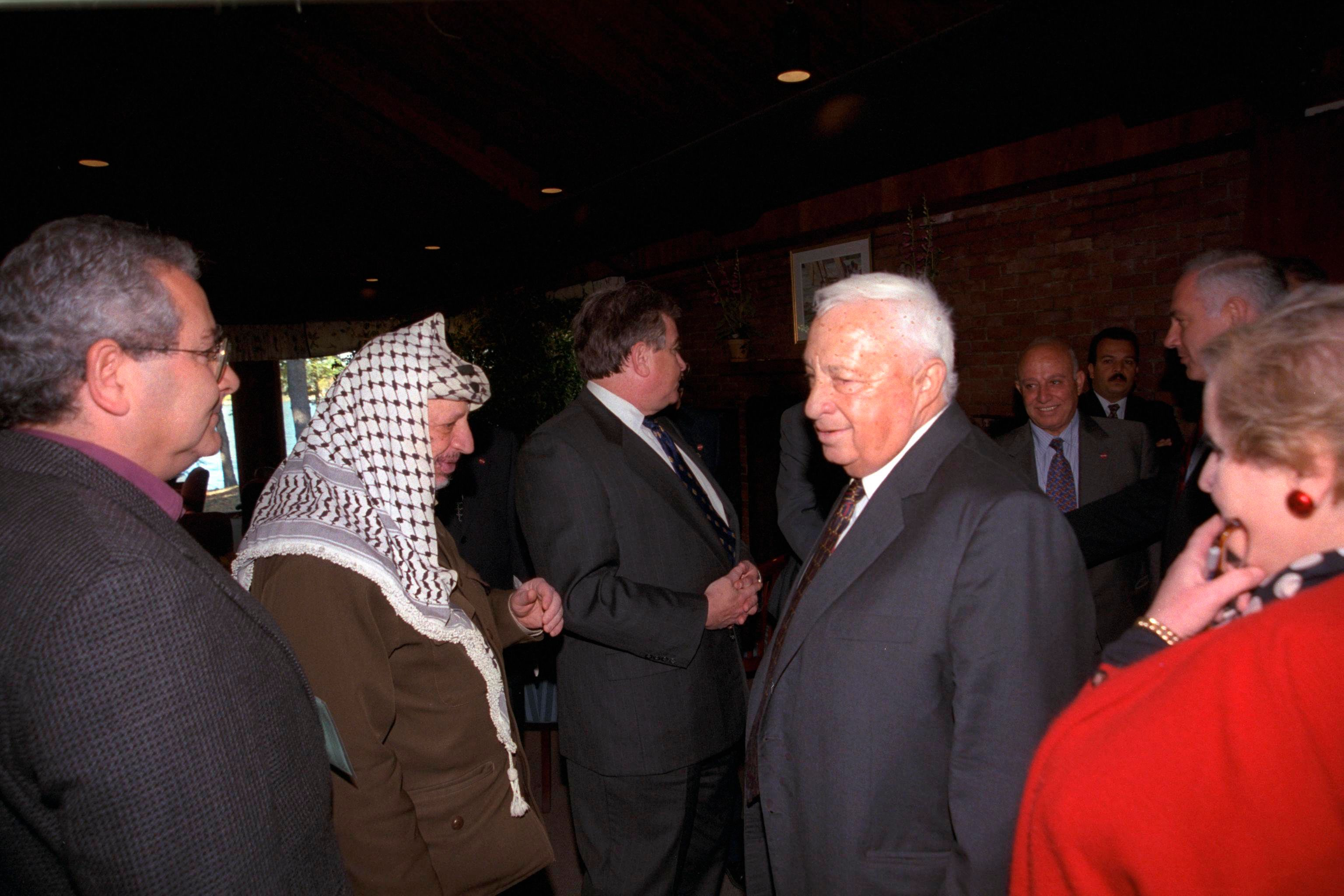 Israel's Foreign Minister Ariel Sharon (4th L) walks past Palestinian Leader Yasser Arafat (2nd L) during the Middle East peace summit at the Wye River Conference centre October 21, 1998, in this handout picture released by the Israeli Government Press Office (GPO). REUTERS/Avi Ohayon/GPO/Handout (UNITED STATES - Tags: POLITICS) FOR EDITORIAL USE ONLY. NOT FOR SALE FOR MARKETING OR ADVERTISING CAMPAIGNS. THIS IMAGE HAS BEEN SUPPLIED BY A THIRD PARTY. IT IS DISTRIBUTED, EXACTLY AS RECEIVED BY REUTERS, AS A SERVICE TO CLIENTS. ISRAEL OUT. NO COMMERCIAL OR EDITORIAL SALES IN ISRAEL