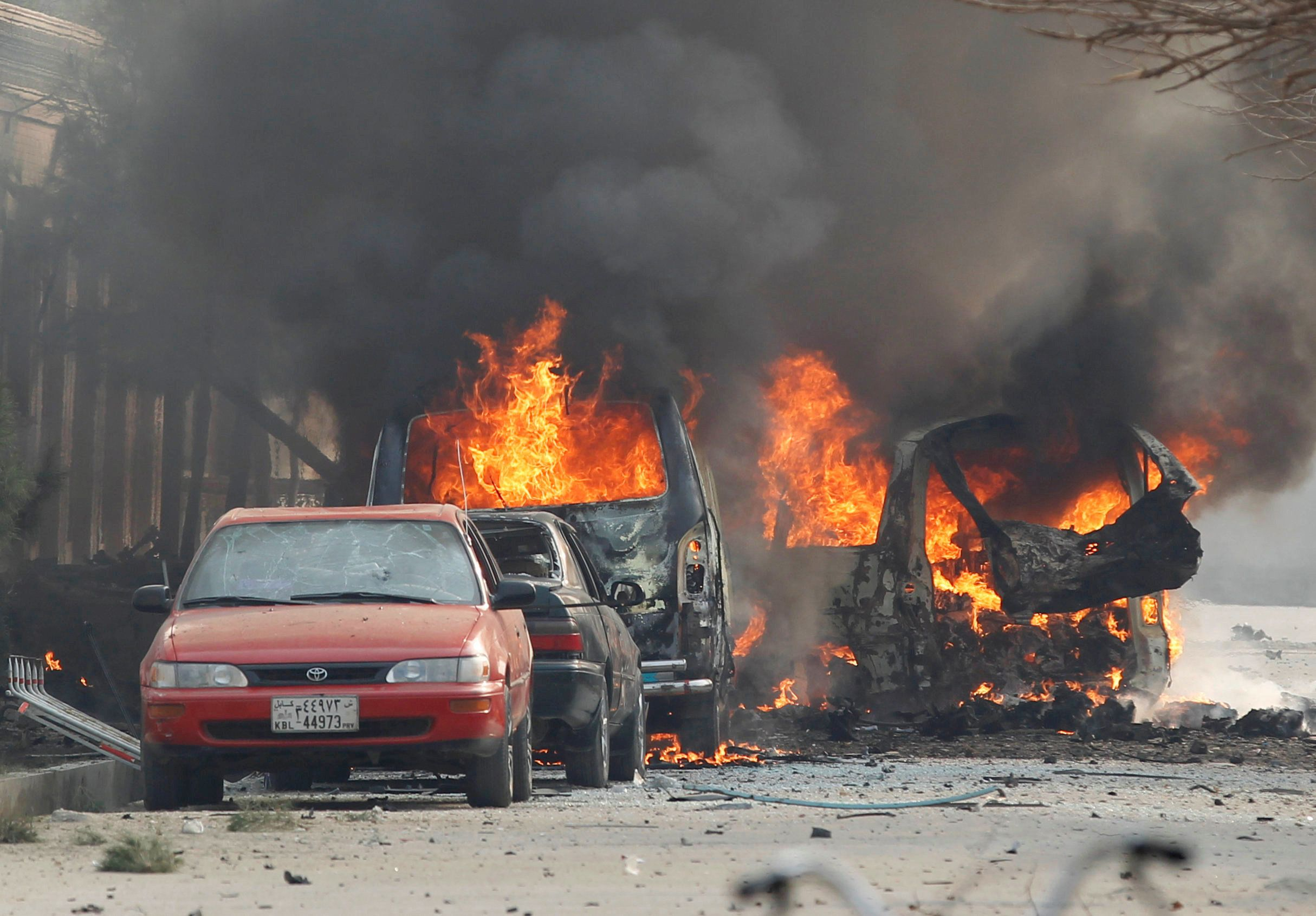 Vehicles are seen on fire after a blast in Jalalabad.