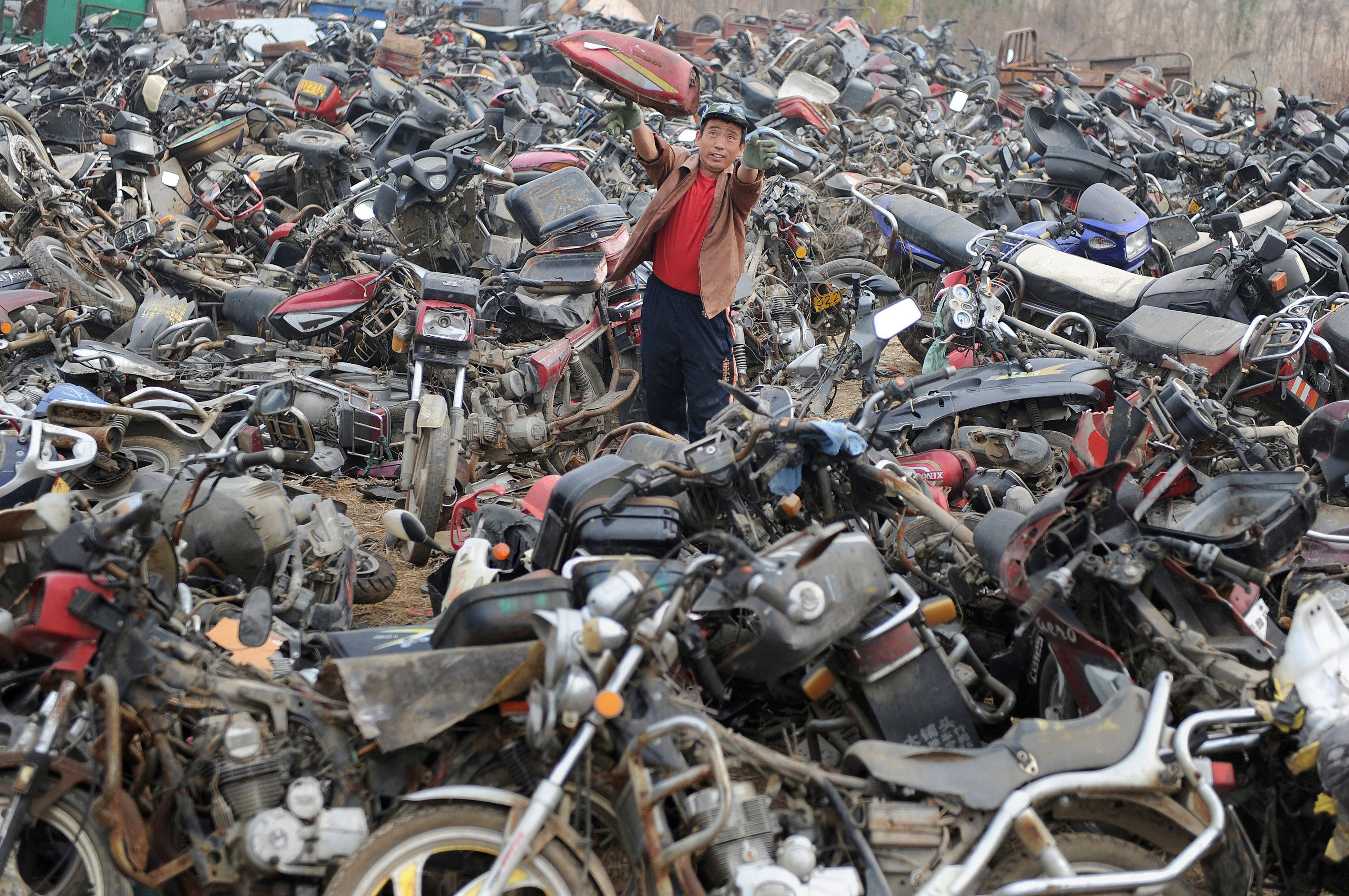 A laborer disassembles motorcycles at a recycling factory in Hefei, Anhui province, China in