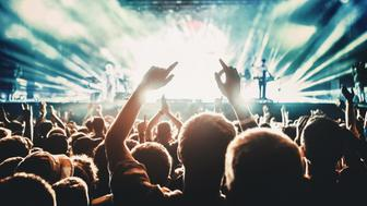 Rear view of people cheering at concert during music festival.Large group of unrecognizable adults with their arms raised.Some of them holding beer cans,some are taping the show with phones.There's a stage and a band performing in background,out of focus.Stage is toned cyan blue.