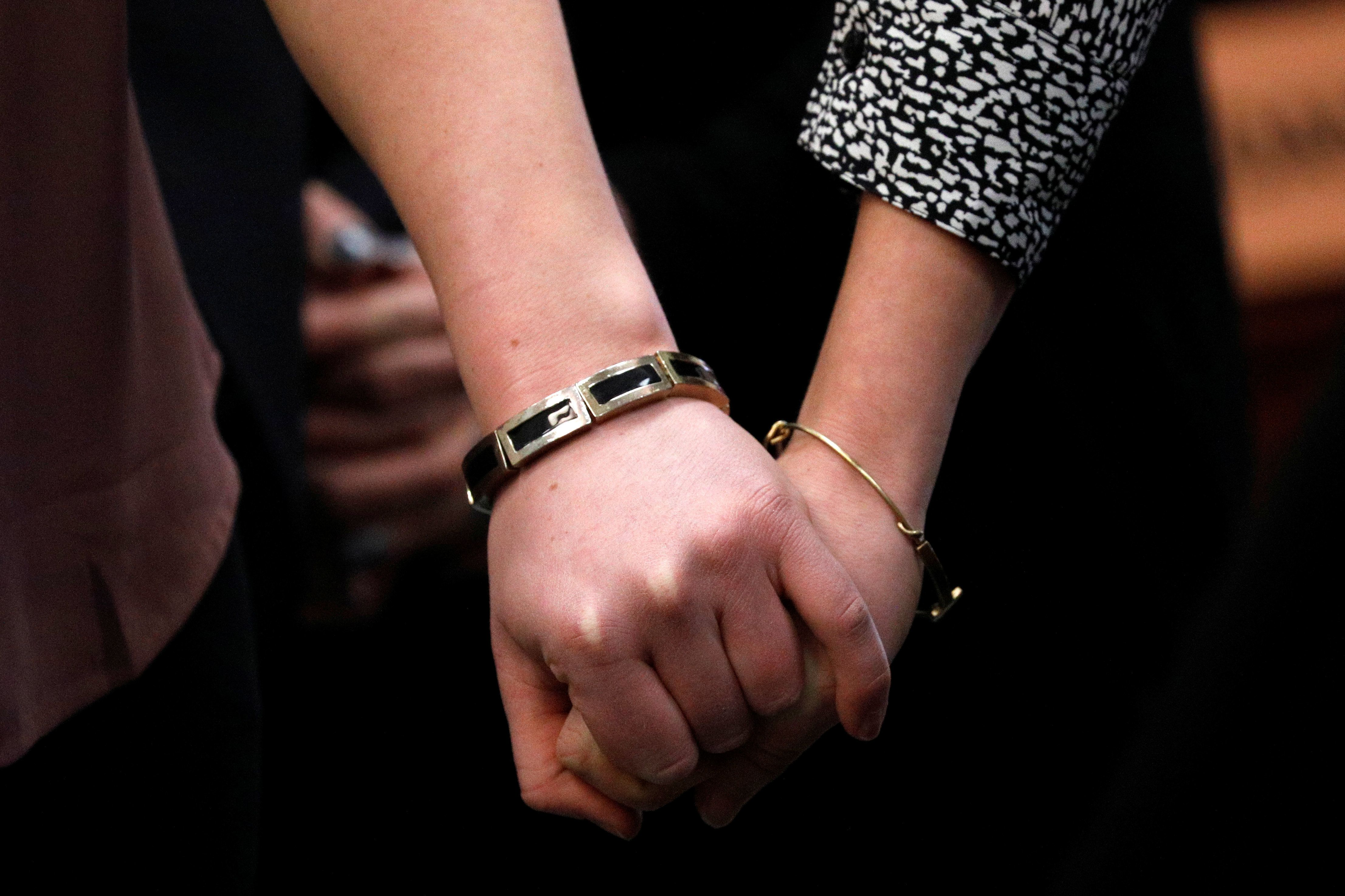 Sisters andNassar survivors Maddie (L) and Kara Johnson (R) hold hands in court on Jan. 19,