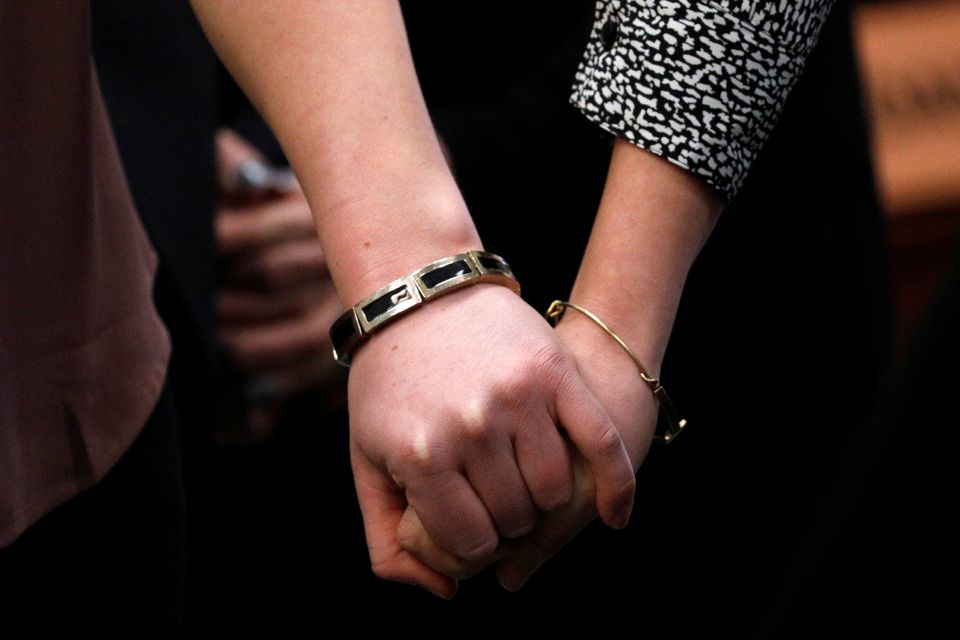 Sisters and Nassar survivors Maddie (L) and Kara Johnson (R) hold hands in court on Jan. 19,