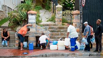 People collect drinking water from pipes fed by an underground spring, in St. James, about 25km from the city centre, on January 19, 2018, in Cape Town.  Cape Town will next month slash its individual daily water consumption limit by 40 percent to 50 litres, the mayor said on January 18, as the city battles its worst drought in a century. / AFP PHOTO / RODGER BOSCH        (Photo credit should read RODGER BOSCH/AFP/Getty Images)