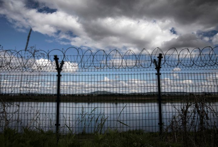 A fence with razor wire marks the Chinese border with North Korea along the Yalu River.