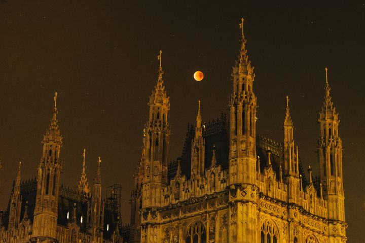 A super blood moon rises over the spires of the House of Parliament on September 28, 2015, in London, United Kingdom.