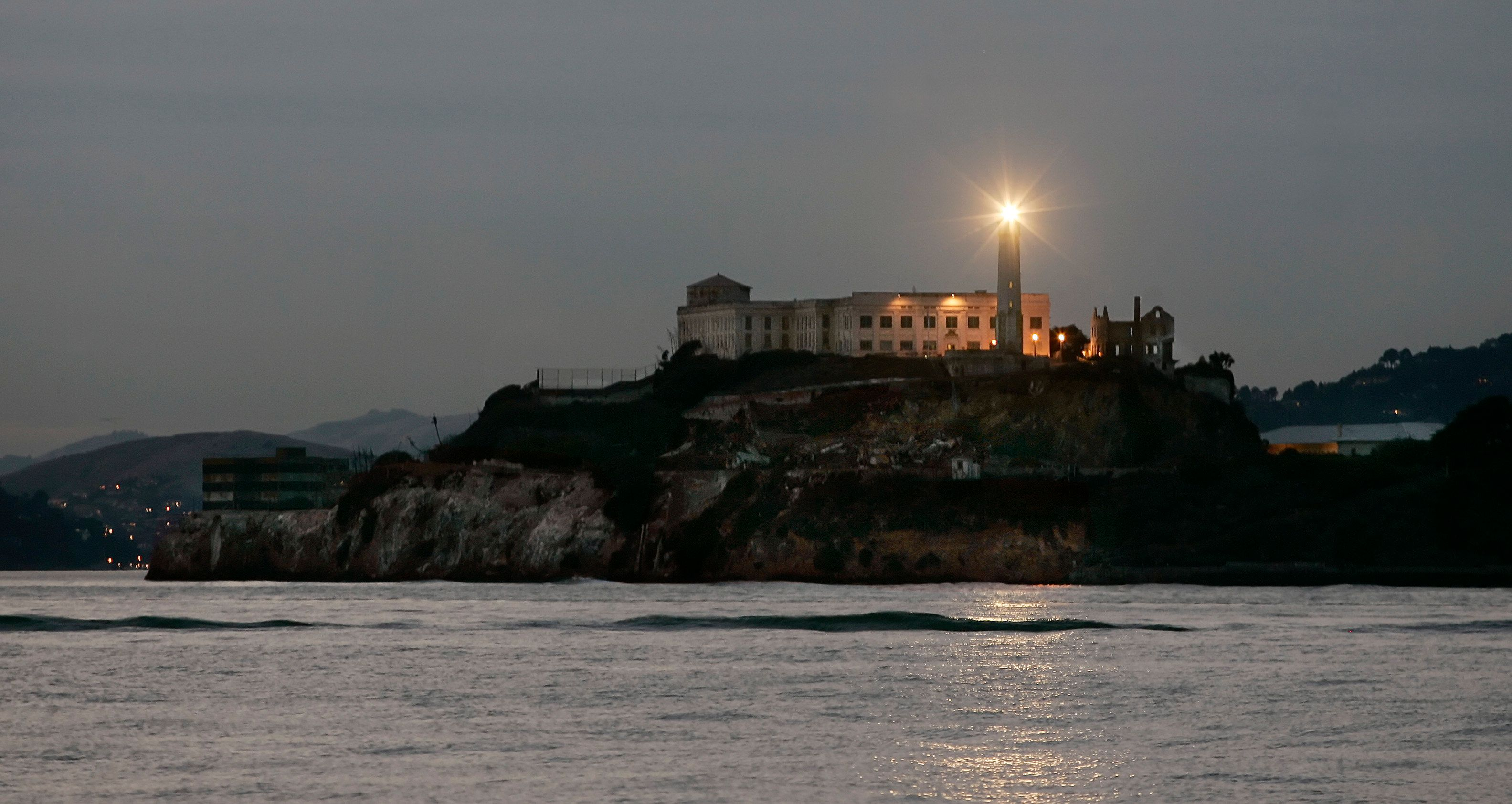 "The lighthouse on the former island prison of Alcatraz flashes at dusk in San Francisco Bay November 8, 2005. First used as a prison by the U.S. Army during the American Civil War, ""The Rock"" became a maximum security penitentiary in 1934 and was closed down in 1964. Today the island is part of the National Parks Service and tours are offered to the notorious island. REUTERS/Andy Clark"