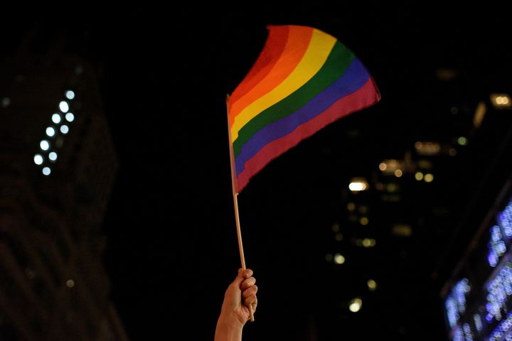 A demonstrator waves a rainbow flag during a dance party in protest of President Donald Trump outside Trump Tower in New York