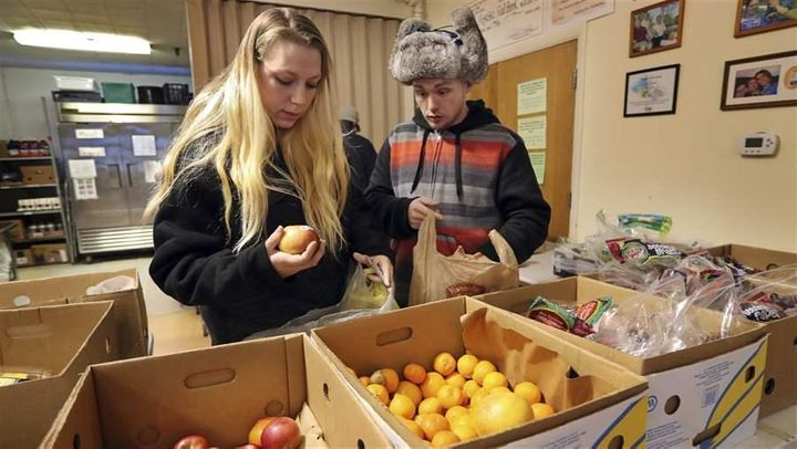 Sunny Larson, left, and Zak McCutcheon gather provisions at a food bank in Maine. Some state lawmakers are proposing new work