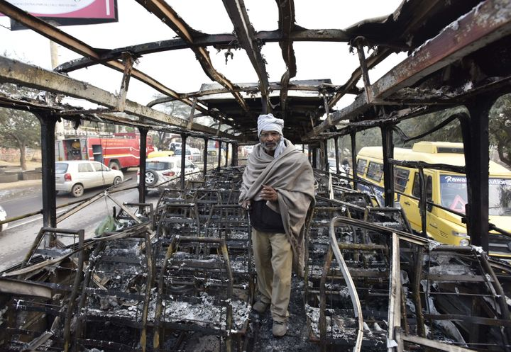 Abus conductorstands inside a bus that was set on fire near the village of Bhondsi in Gurgaon, allegedly by activ