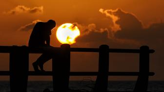 An Acehnese man watches the sunset at Meulaboh beach in Indonesia's Aceh province on June 9, 2017. The devout western province is the only part of the world's most populous Muslim-majority country allowed to implement sharia laws and is often criticised by rights groups, where canings for people caught gambling, drinking alcohol, spending time with members of the opposite sex outside of marriage and having gay sex. / AFP PHOTO / CHAIDEER MAHYUDDIN        (Photo credit should read CHAIDEER MAHYUDDIN/AFP/Getty Images)