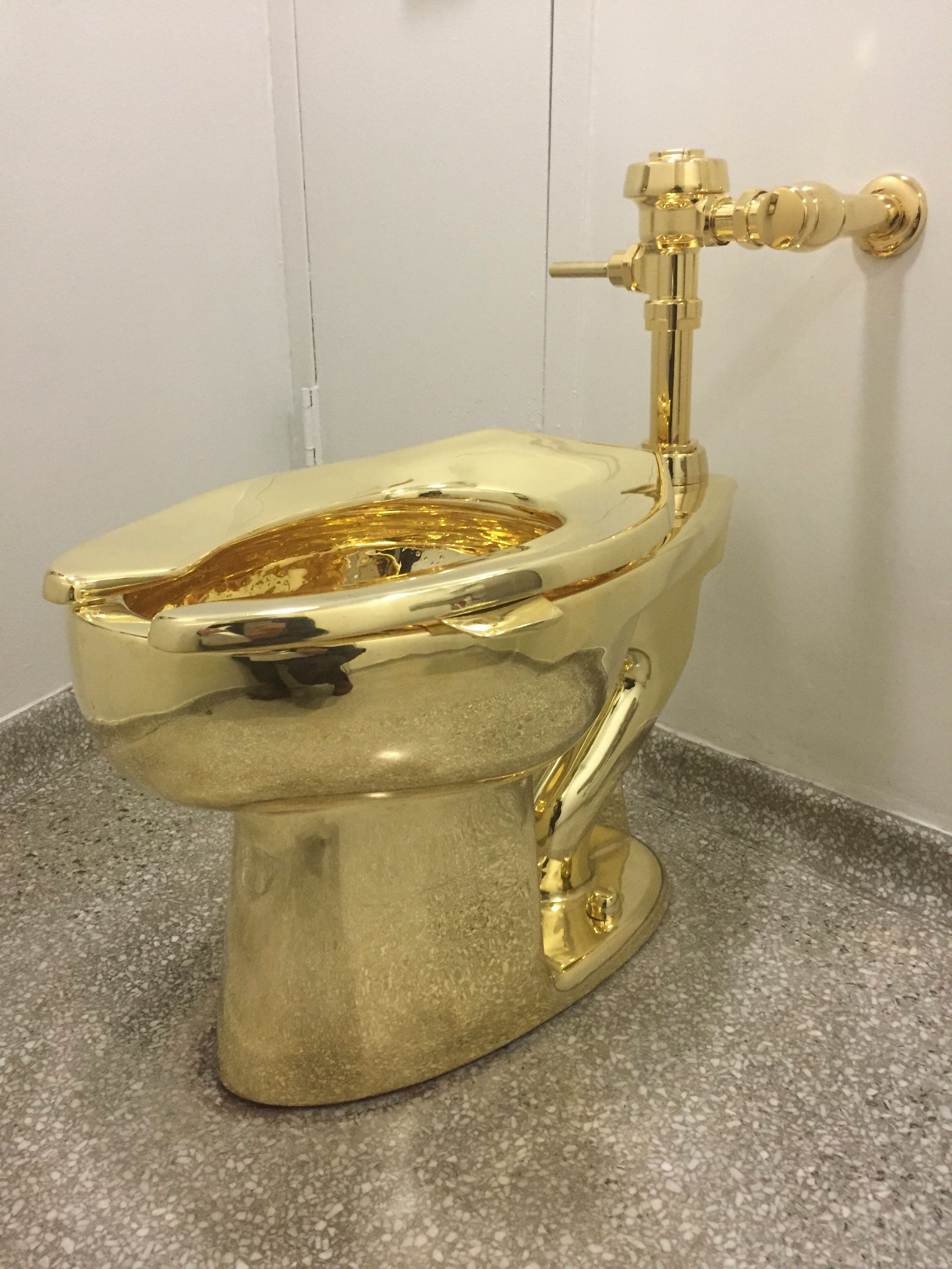 A fully functioning solid gold toilet, made by Italian artist Maurizio Cattelan, is going into public use at the Guggenheim Museum in New York on September 15, 2016.  A guard will be stationed outside the bathroom to protect the work, entitled 'America', which recalls Marcel Duchamp's famous work, 'Fountain'. / AFP / William EDWARDS        (Photo credit should read WILLIAM EDWARDS/AFP/Getty Images)