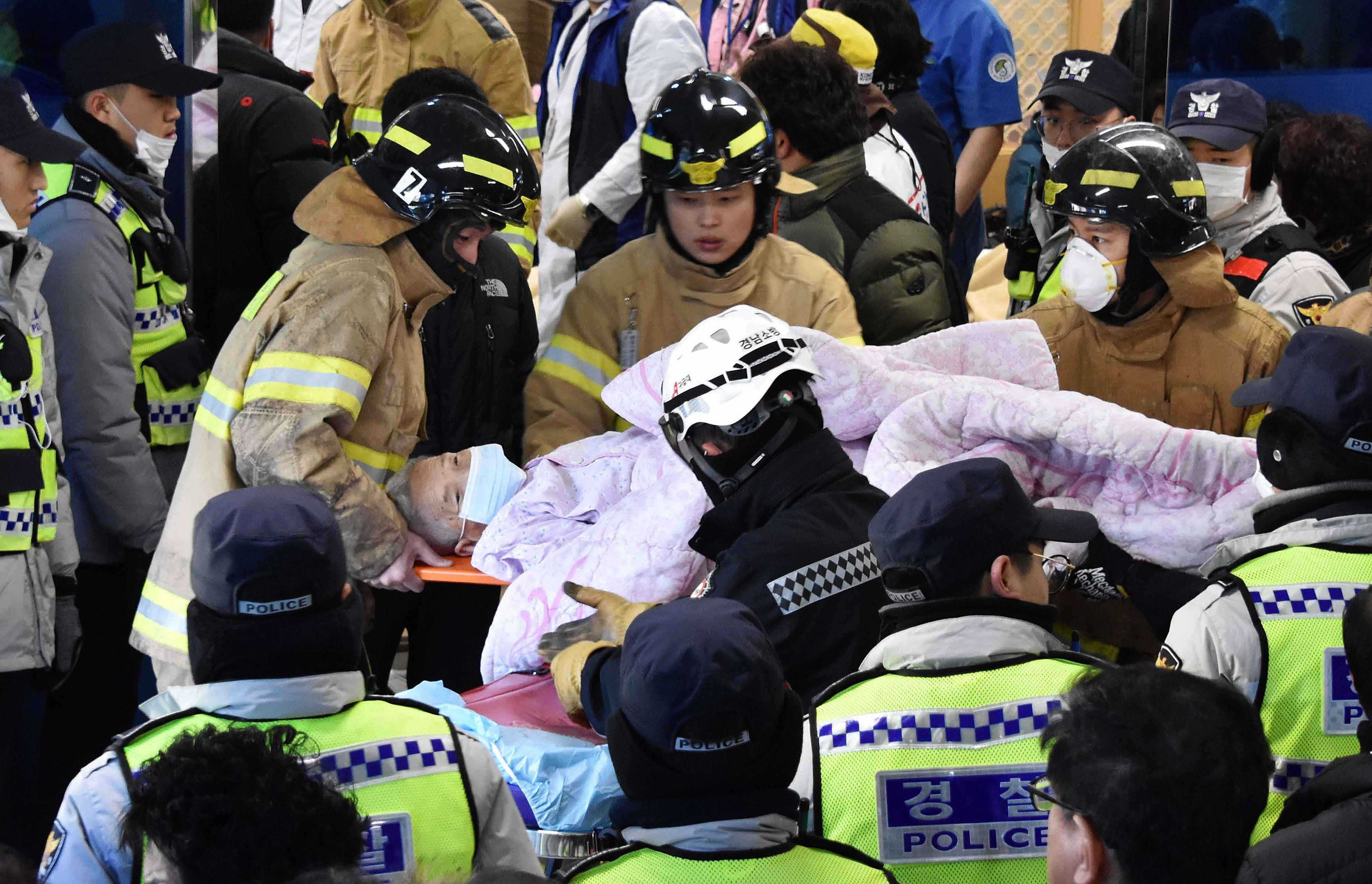 MIRYANG, SOUTH KOREA - JANUARY 26: (SOUTH KOREA OUT) In this handout picture provided by the Kim Gu Yeon-Gyeongnam Domin Ilbo, Rescue workers remove a survivor from a hospital fire on January 26, 2018 in Miryang, South Korea. 40 people were killed in a fire at a hospital in the southeastern city of Miryang early Friday, with the number of casualties likely to rise further.  (Photo by Kim Gu-Yeon/Gyeongnam Domin Ilbo via Getty Images)