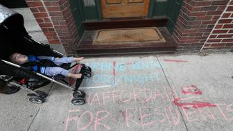 BOSTON, MA - OCTOBER 5: A family strolls along Oak Street in the Chinatown neighborhood of Boston on Oct. 5, 2017, where protestors have marked the sidewalk in front of an Airbnb rental. Chinatown residents and activists are protesting Airbnb and other short term rental groups that they claim are pushing out local families. (Photo by Suzanne Kreiter/The Boston Globe via Getty Images)