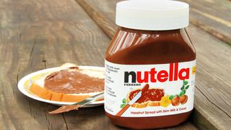 West Palm Beach, USA - October 27, 2011: Product shot of a container of Nutella hazelnut and cocoa spread. A saucer with a slice of bread freshly spread with a layer of Nutella is in the background.