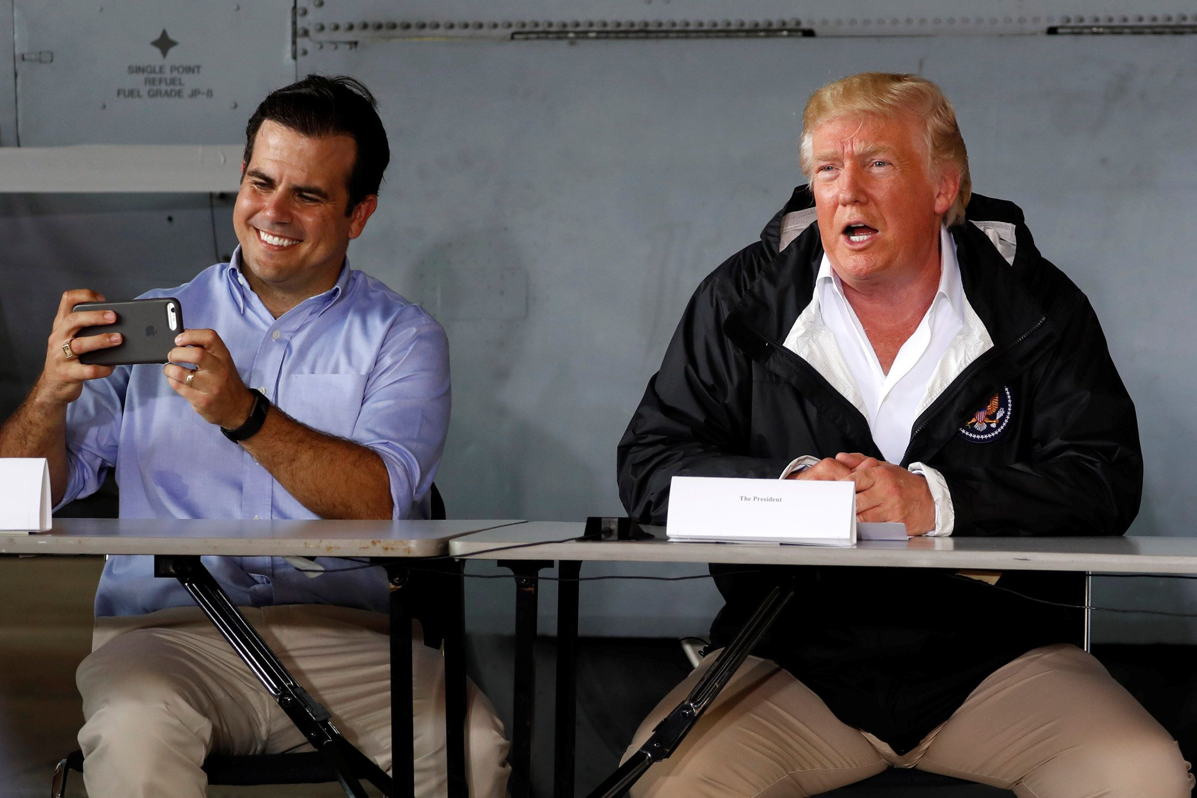 Puerto Rico Gov. Ricardo Rossello, left, takes a picture as he and President Donald Trump receive a briefing on hurricane rel