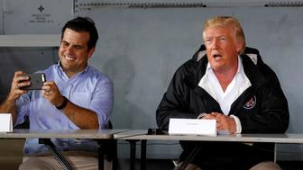 Puerto Rico Governor Ricardo Rossello (L) takes a picture as he and U.S. President Donald Trump receive a briefing on hurricane relief efforts in a hangar at Muniz Air National Guard Base in Carolina, Puerto Rico, U.S. October 3, 2017. REUTERS/Jonathan Ernst