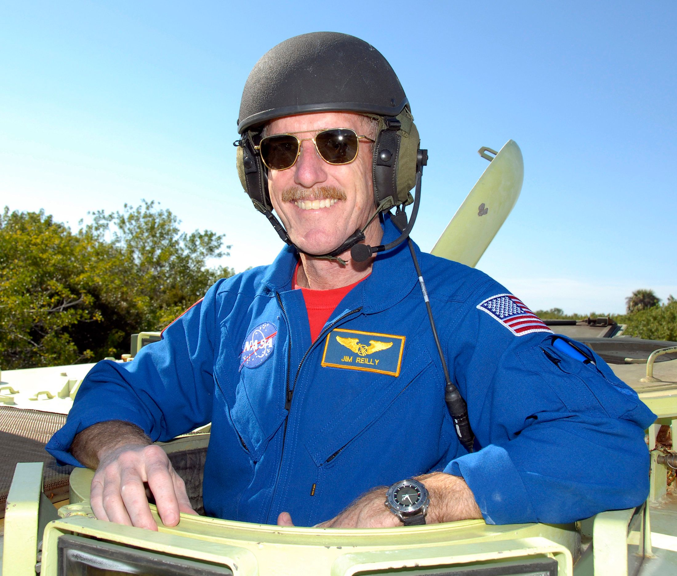 Mission specialist James Reilly ll poses for a photo after driving the M-113 armored personnel carrier at the Kennedy Space Center, Cape Canaveral, Florida, February 22, 2007. The crew of the space shuttle Atlantis arrived  at  Kennedy Space Center  for a dress rehearsal launch countdown.  Atlantis is scheduled to launch in early March with a crew of six on a 11-day mission to the International Space Station.  FOR EDITORIAL USE ONLY   REUTERS/NASA Kim Shiflett  (UNITED STATES)