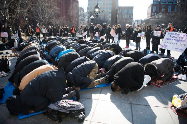 "Congregants bow in prayer during the ""Jummah Prayer: NoBanJFK, 1 Year Later"" event in Washington Square Park in New York"