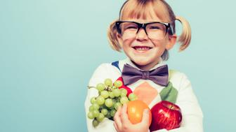 A young nerd girl with glasses and bow tie is excited for healthy eating and fruit. She is holding an apple, an orange and some green grapes and has an excited expression on her face.