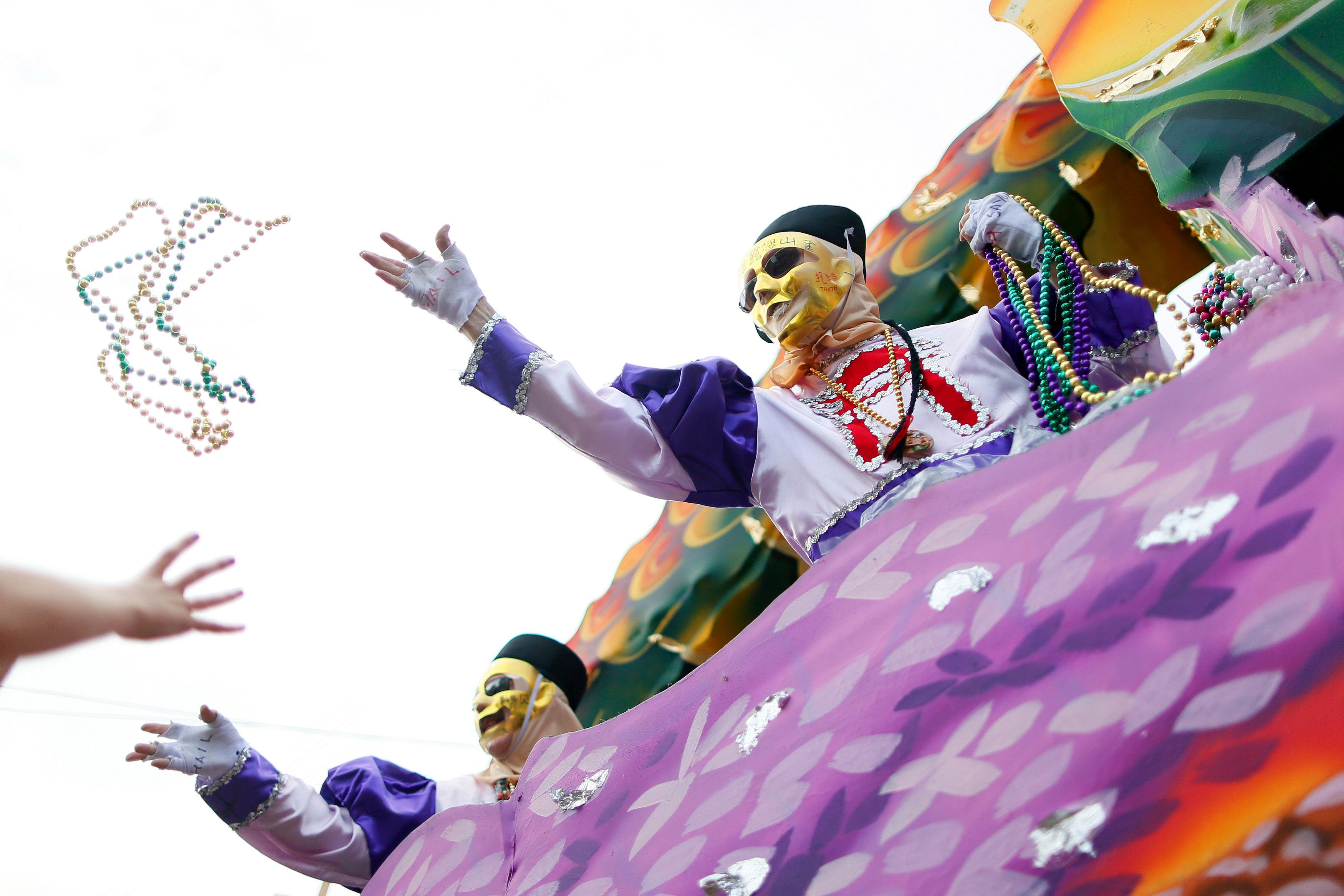 A member of the Krewe of Thoth throws beads during a Mardi Gras parade in New Orleans, Louisiana February 15, 2015. REUTERS/Jonathan Bachman (UNITED STATES - Tags: SOCIETY)