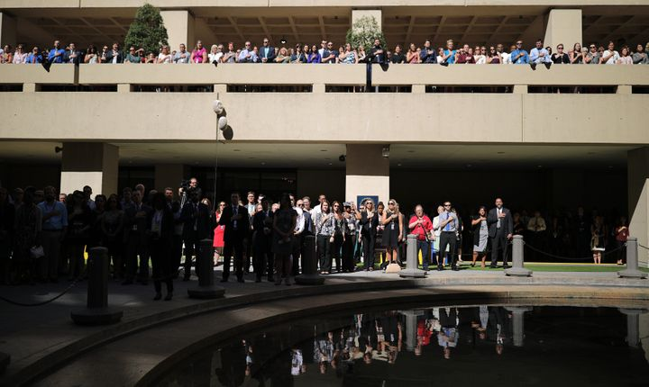 FBI agents and employees stand with their hands over their hearts for the national anthem at September's installation ceremon