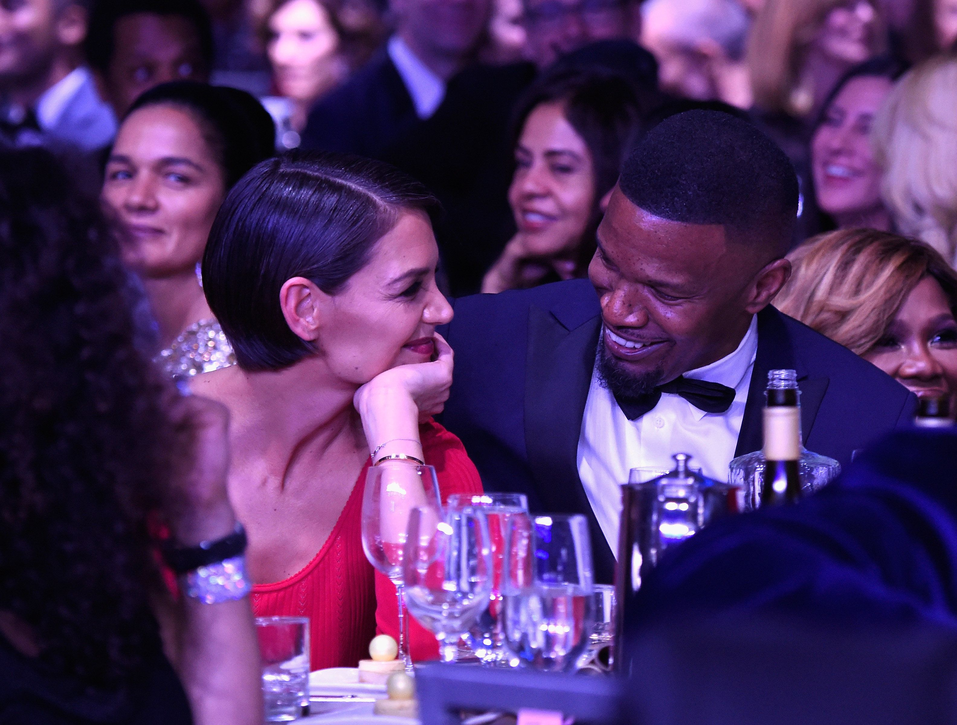 Katie Holmes and Jamie Foxx smile at each other at a pre-Grammy Awards event on Saturday night.
