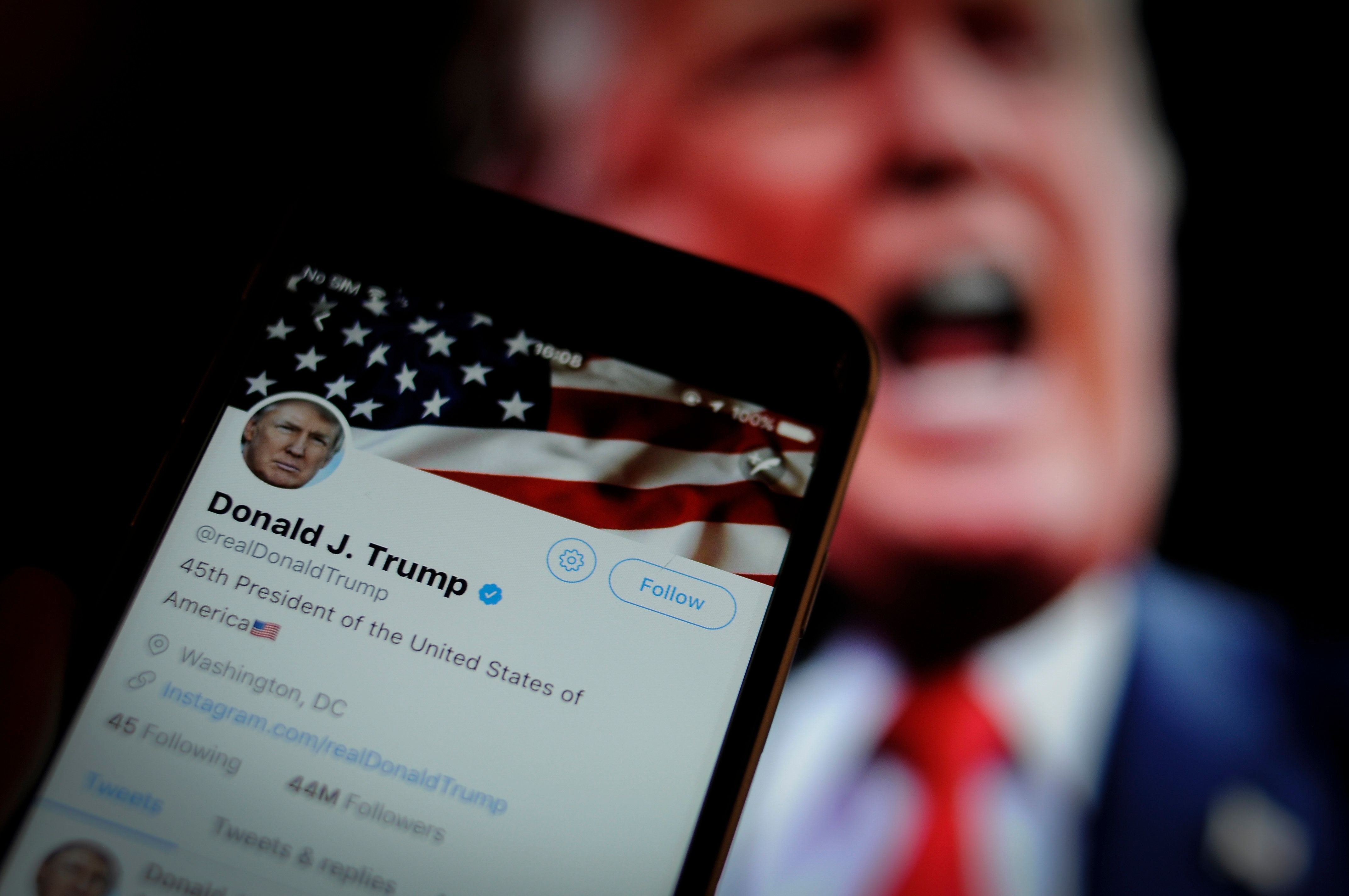The Twitter app is seen with an image of US president Donald Trump in the background in this photo illustration on December 4, 2017. (Photo by Jaap Arriens/NurPhoto via Getty Images)