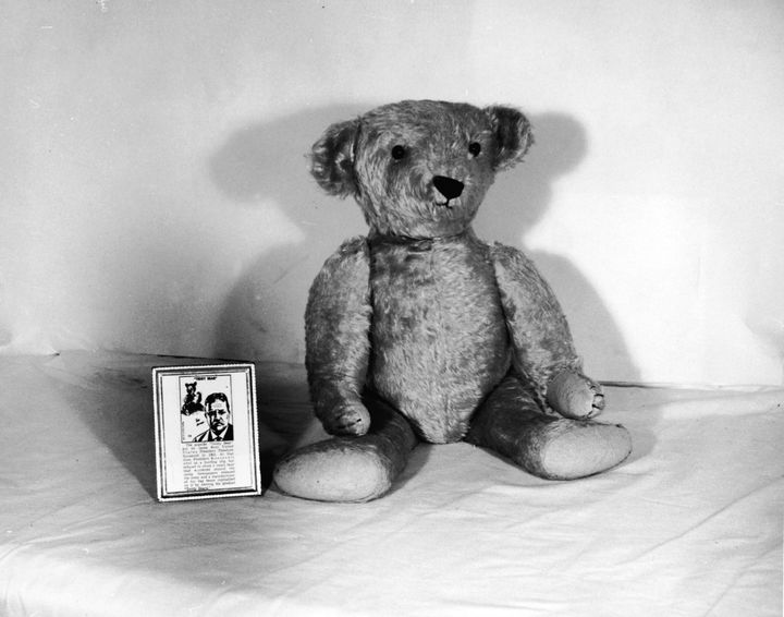 A teddy bear in the 1950s sits next to its tag explaining its link to President Theodore Roosevelt.
