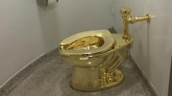 A fully functioning solid gold toilet, made by Italian artist Maurizio Cattelan, is going into public use at the Guggenheim Museum in New York on September 15, 2016.  A guard will be stationed outside the bathroom to protect the work, entitled 'America', which recalls Marcel Duchamp's famous work, 'Fountain'. / AFP PHOTO / William EDWARDS        (Photo credit should read WILLIAM EDWARDS/AFP/Getty Images)
