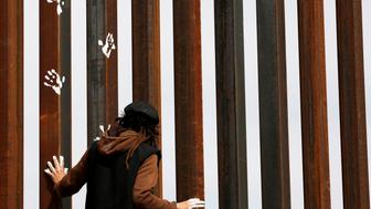 An activist paints the U.S.-Mexico border wall between Ciudad Juarez and New Mexico as a symbol of protest against U.S. President Donald Trump's new immigration reform in Ciudad Juarez, Mexico February 26, 2017. REUTERS/Jose Luis Gonzalez       TPX IMAGES OF THE DAY