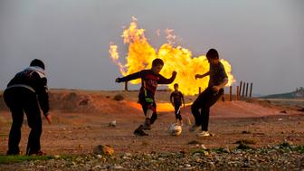 REGIONAL GOVERNMENT OF KURDISTAN, IRAQ - 2015. Teenagers playing football nearby a refinery. Regional governorate of Iraqi Kurdistan stated that its oil production holds 30% of Iraq total production, the observer considers the production as 10% of the country's. Kirkuk area is one of the biggest oil producing center of the region. (Photo by Reza/Getty Images)