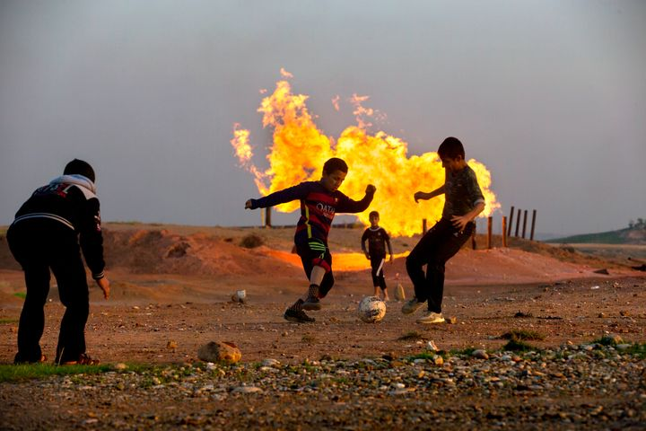 Teenagers play near an oil refinery outside the city of Kirkuk in Iraqi Kurdistan.