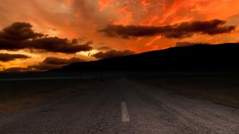 Halloween background - skull on the road and red sunset